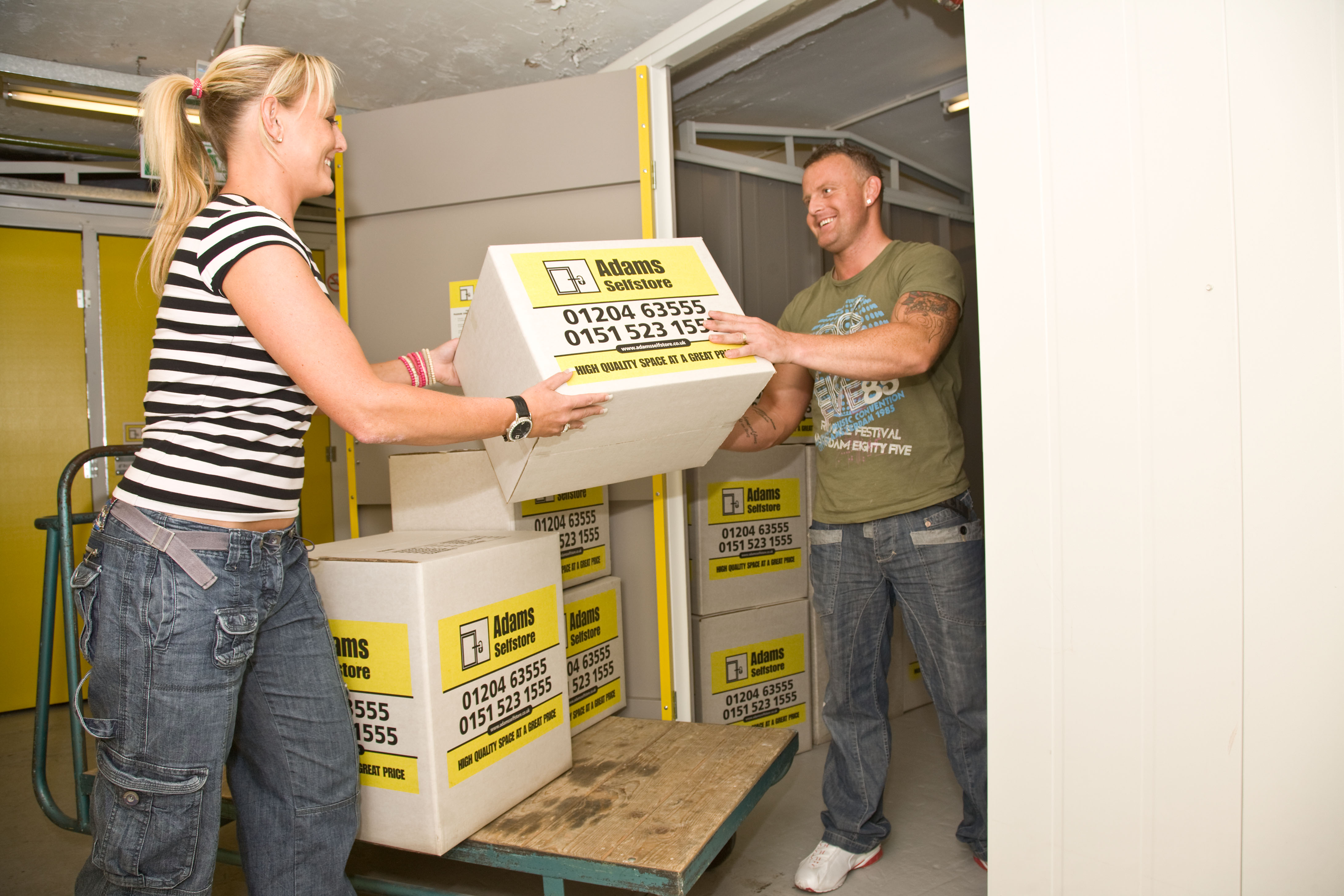 Couple loading items in to their storage room.